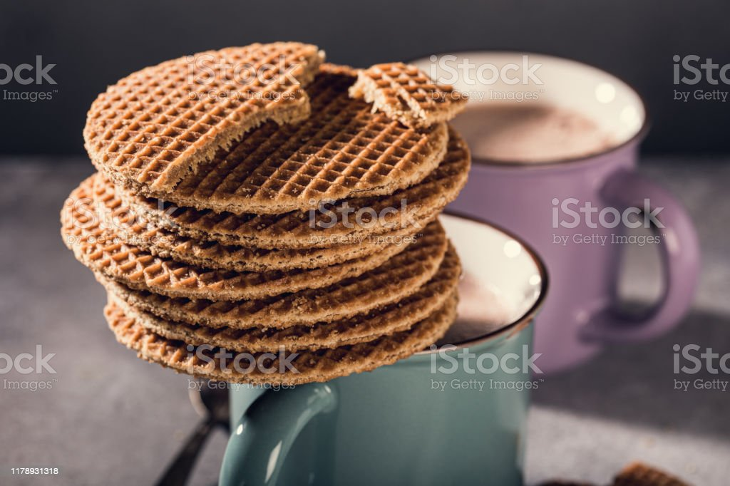 Traditional dutch cookies syrupwaffles Old mug with chocolate milk and traditional dutch cookies stroopwafels on gray background with copy space. Retro style toned. Backgrounds Stock Photo