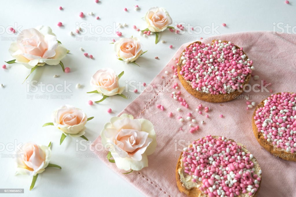 traditional Dutch food pink muisjes, aniseed on rusk, roses, for celebration birth of a daughter stock photo
