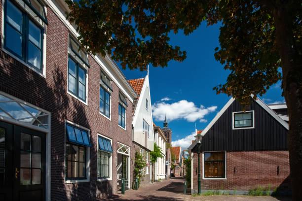traditionele nederlandse huizen van hout gebouwd met typische architectuur en met felle kleuren geschilderd. - beemster stockfoto's en -beelden