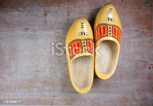 istock Traditional Dutch, Netherlands, Holland, wooden clogs for souvenir or traveling etc isolated on wooden background with copy space for your own text 1161609177