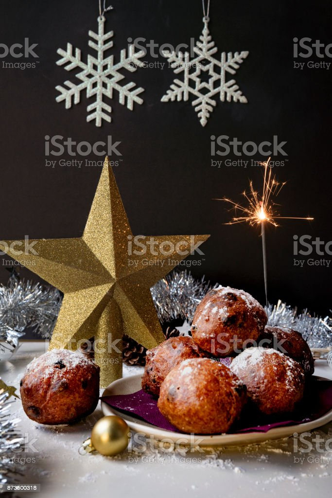 traditional Dutch oliebollen, oil dumpling or fritter, with wooden spoon, for New Year's Eve, with sparkler stock photo