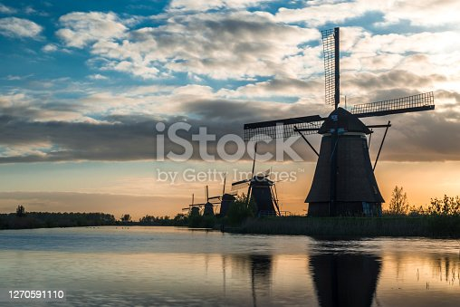 A collection of 18th Century traditional Dutch windmills reflected in water at sunrise, at Kinderdijk in South Holland.