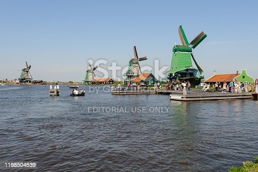 Zaanse Schans, Netherlands - 22 April 2019: Tourists sightseeng famous traditional Dutch windmills in Zaanse Schans, is a typical small village within Amsterdam area.