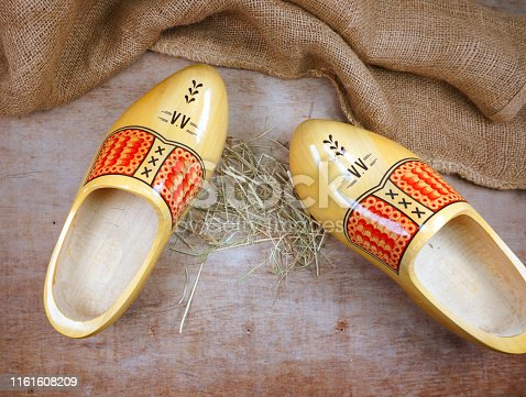 istock Traditional dutch wooden clogs isolated on wooden background with burlap hessian and hay straw 1161608209
