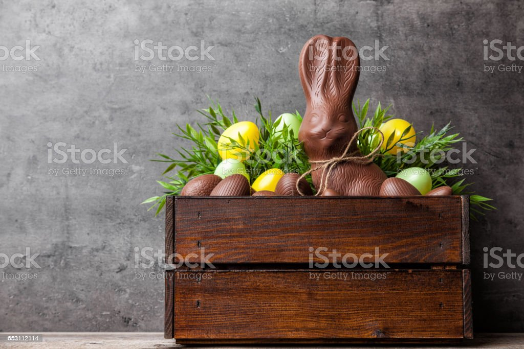 Traditional Easter chocolate bunny and eggs inside a wooden crate stock photo