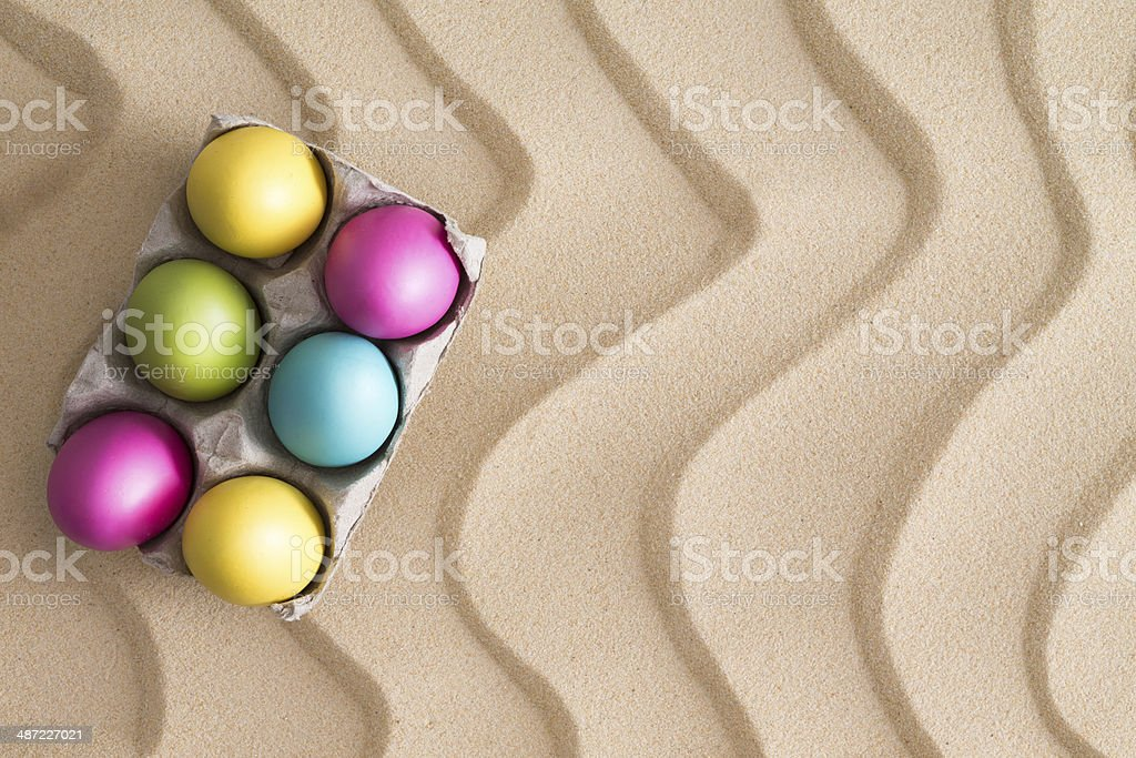 Traditional Easter Egg hunt at the beach Traditional Easter Egg hunt at the beach with a box of colorful painted eggs hidden on golden sand with a decorative wavy pattern and copyspace for your seasonal greeting Beach Stock Photo