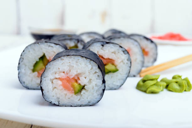 Traditional eastern dish with salmon sushi rolls on a white plate. stock photo