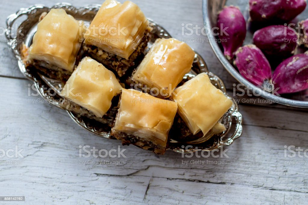 traditional eastern tasty baklava and prickly pear fruits on the white wooden table stock photo