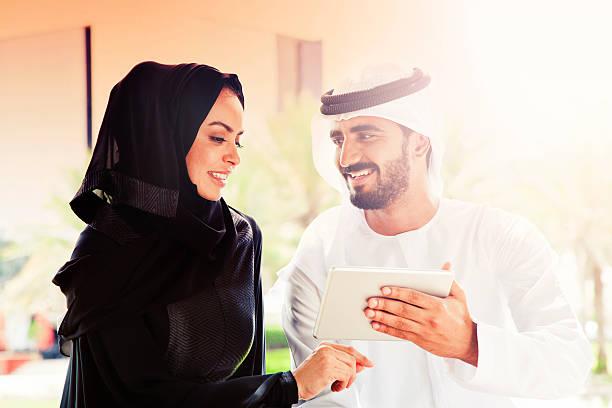 traditionelle emiratische junge familie surfen im internet - hochzeitsreise dubai stock-fotos und bilder