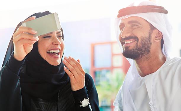 traditionelle emiratische junge familie, die ein selfie - hochzeitsreise dubai stock-fotos und bilder