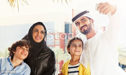 472869308 istock photo Traditional Emirati young family taking a selfie 472310926