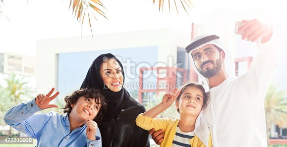 472869308 istock photo Traditional Emirati young family taking a selfie 472310928