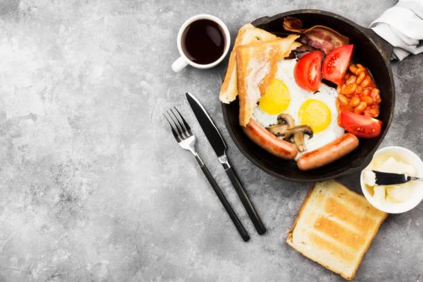 traditionelles englisches frühstück - speck, würstchen, spiegelei, tomaten, bohnen, champignons, toast mit butter - in der küche, pan und kaffee auf einem grauen hintergrund. ansicht von oben, raum zu kopieren. essen-hintergrund - gefüllte eier stock-fotos und bilder