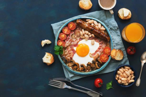 traditionelles englisches frühstück auf blauem grund. spiegelei mit pilzen, bohnen, tomaten, wurst und speck. ansicht von oben, raum zu kopieren. - gefüllte eier stock-fotos und bilder