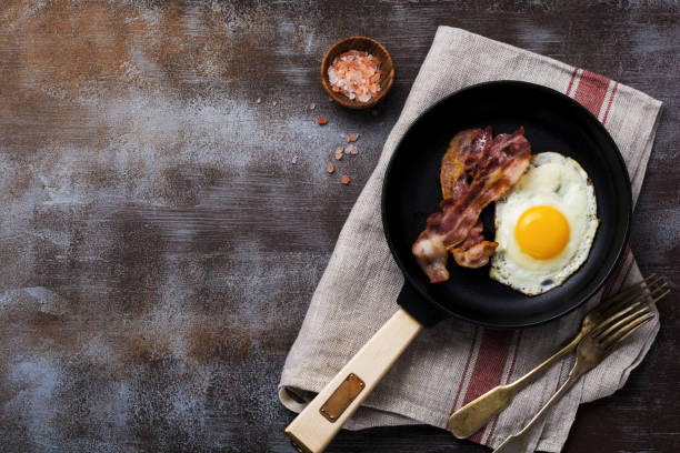 Traditional English breakfast with fried eggs and bacon in cast iron pan on dark concrete background. Top view. Traditional English breakfast with fried eggs and bacon in cast iron pan on dark concrete background. Top view. low carb diet stock pictures, royalty-free photos & images