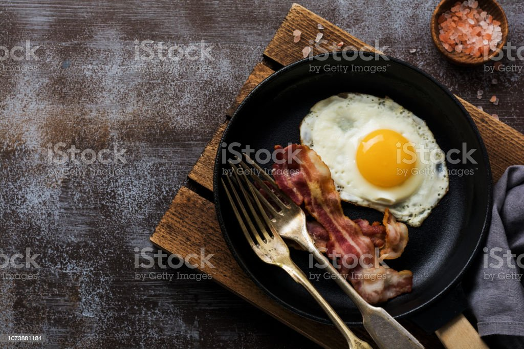 Traditional English breakfast with fried eggs and bacon in cast iron pan on dark concrete background. Top view. royalty-free stock photo