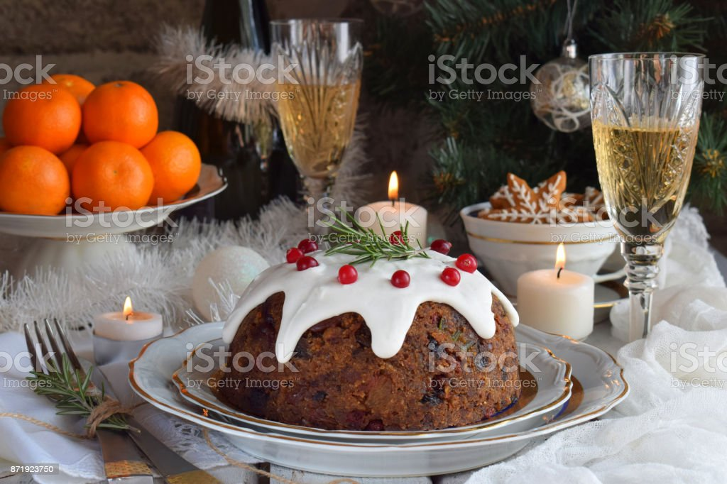 Traditional english Christmas steamed pudding with winter berries, dried fruits, nut in festive setting with Xmas tree, burning candle, tangerines and glass of white wine, champagne. Fruit cake stock photo