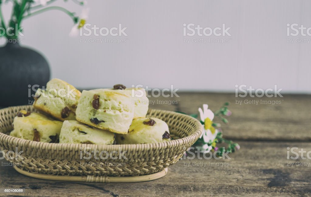 Traditional English pastry: scones. Homemade raisin scones in basket on rustic wood table. Raisin scones for afternoon tea,cream tea,high tea in devon shire or cornish style. Vintage tone concept. stock photo