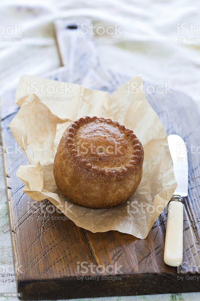 Traditional English Pork Pie on a chopping baord royalty-free stock photo