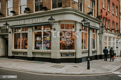istock Traditional english tavern facade at evening, with people and lights inside, in London, England. 1071356652
