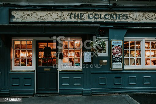 istock Traditional english tavern facade at evening, with people and lights inside, in London, England. 1071356654
