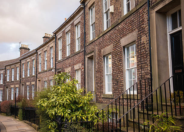 Traditional English terraced houses in Newcastle A curving row of traditional brick-built terraced townhouse properties in Newcastle, England. northeastern england stock pictures, royalty-free photos & images