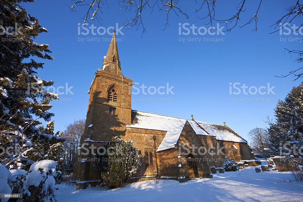 Traditional English village churchyard in snow royalty-free stock photo