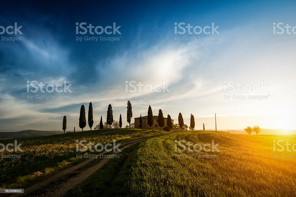Traditional farm on Tuscany hill with cypresses at sunset stock photo