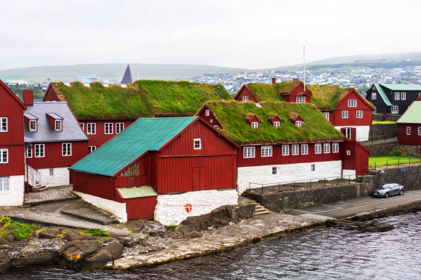 Traditional faroese buildings painted in red with grass roofs in harbor of Torshavn. stock photo