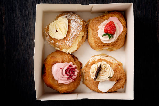 traditional fastelavn cakes or danish cream cakes in a box. - fastelavn stock pictures, royalty-free photos & images