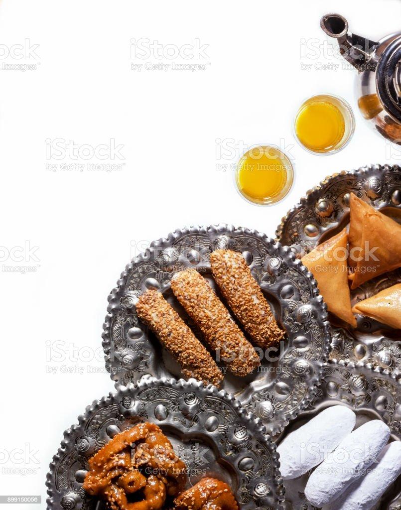 Thé et biscuits marocains festives traditionnelles. Plats avec biscuits marocains et des grignotines. Isolé sur fond blanc. - Photo