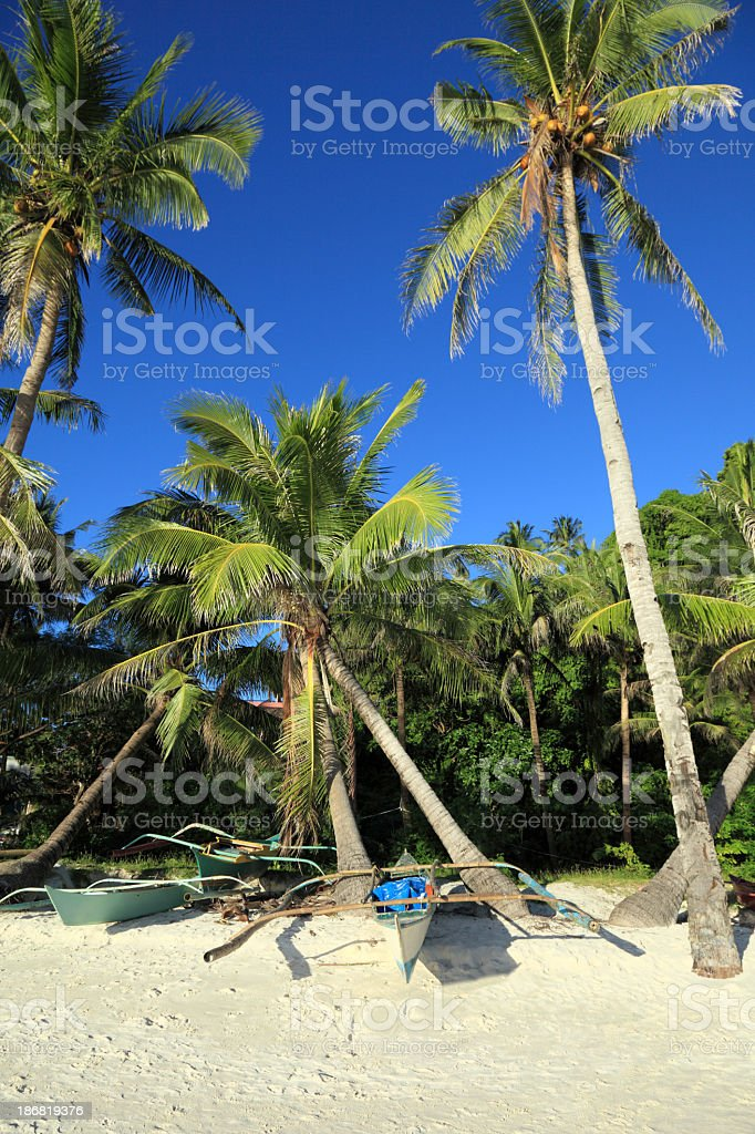 Traditional Filipino outrigger boats stranded on the beach royalty-free stock photo
