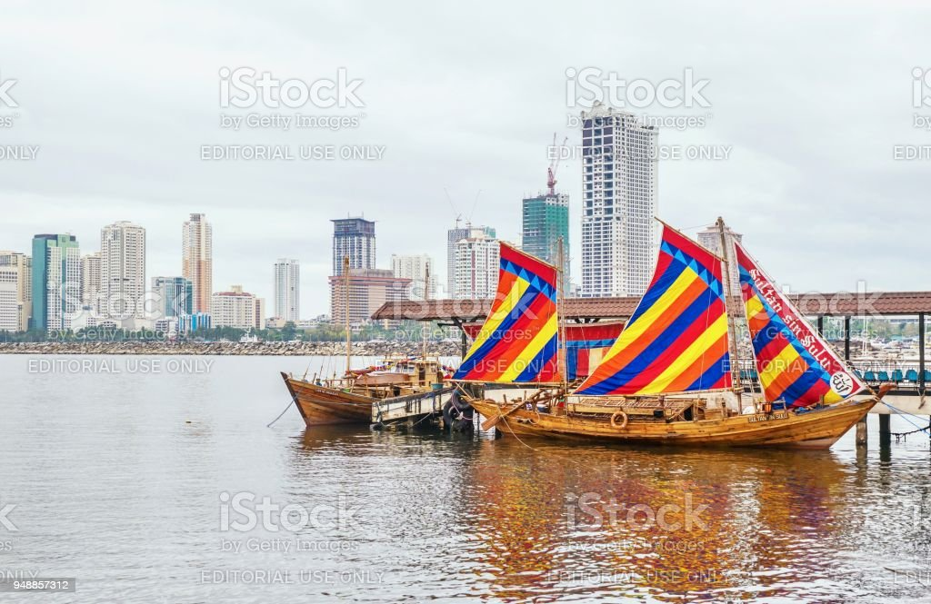 A traditional Filipino wooden sailboat (named 'The Sultan Sin Sulu') with colorful, striped, hoisted sails is docked in Manila Bay, with a modern skyline in the background. stock photo
