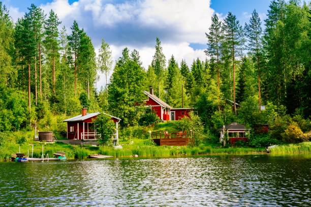 a traditional finnish wooden cottage with a sauna and a barn on the lake shore. summer rural finland. - finland stock pictures, royalty-free photos & images
