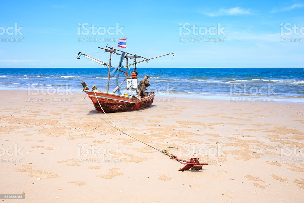 Traditional fishing boat anchor on beach, blue sea and sky stock photo