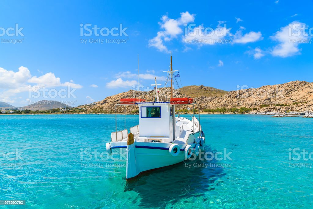 Traditional fishing boat on azure crystal clear sea water in Kolymbithres bay, Paros island, Greece stock photo