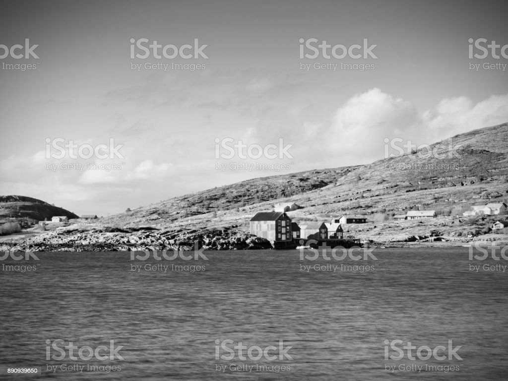 Traditional fishing village. Cottages at the coast on the rocky island. Red white building shinning stock photo