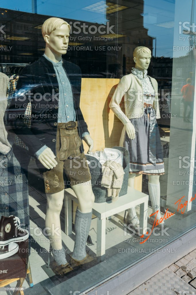 Traditional folk Bavarian clothes on a mannequin man and woman in a shop window front stock photo