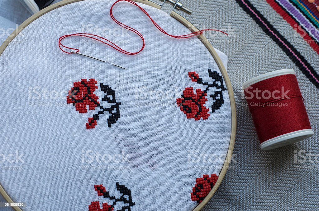 Traditional folk embroidery cross on a wooden hoop, floral motif