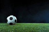 Traditional football on an illuminated empty sports field at night backlit by bright spotlights in a low angle view with shadow, mist and copy space