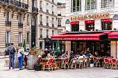 Paris, France - June 16, 2017: A traditional restaurant A La Place St Georges in Paris, in St.Georges Square. Parisians and tourists enjoy food and drinks on the terrace in the summer day.