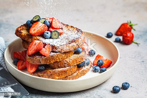 Traditional French toast with blueberries, strawberries and powdered sugar on a white plate.