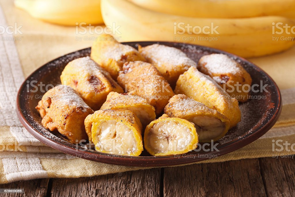 Traditional fried bananas sprinkled with powdered sugar close-up stock photo