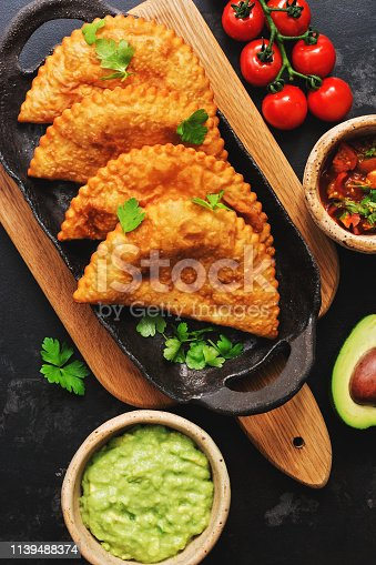 istock Traditional fried empanadas served with tomato and avocado sauce on a dark background. Top view, copy space 1139488374