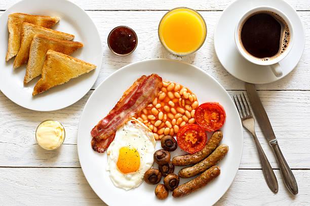 traditional fried english breakfast with orange juice and coffee - gefüllte eier stock-fotos und bilder