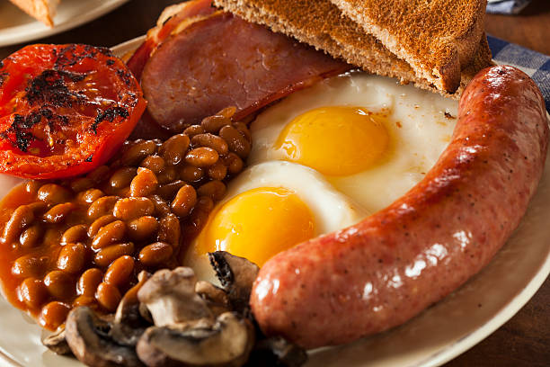 Traditional Full English Breakfast Traditional Full English Breakfast with Eggs, Bacon, Sausage, and Baked Beans full stock pictures, royalty-free photos & images
