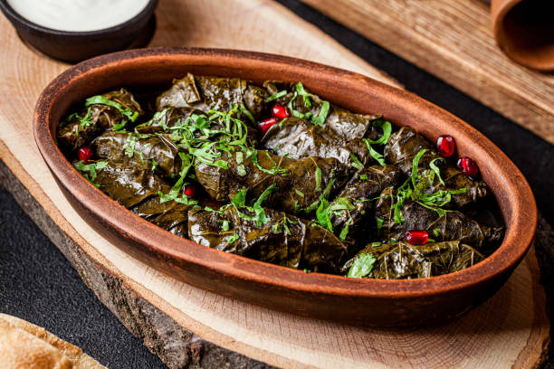 "Traditional Georgian and Armenian cuisine. The dish ""Dolma"" or ""Tolma"". Cabbage rolls of grape leaves with rice and minced meat. Copy space, background image"