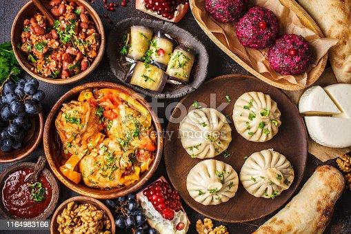 Traditional Georgian cuisine background. Khinkali, phali, chahokhbili, lobio, cheese, eggplant rolls on dark background, top view.
