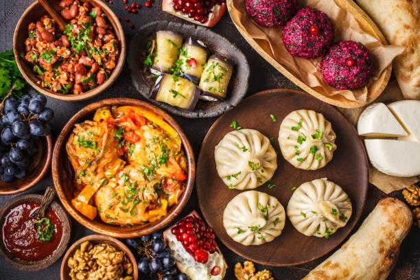 Traditional Georgian cuisine background. Khinkali, phali, chahokhbili, lobio, cheese, eggplant rolls, dark background. stock photo