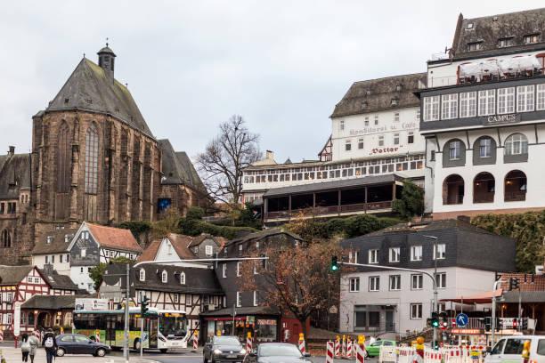 traditionelle deutsche bauten und universitätskirche marburg mit herbstlichem grauen himmel - marburg uni stock-fotos und bilder
